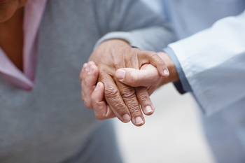 Closeup of an old woman's hand being held by a doctor