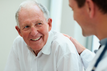 Happy old man having a casual talk with a doctor