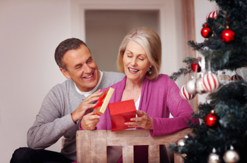 Cheerful mature woman with husband opening Christmas present
